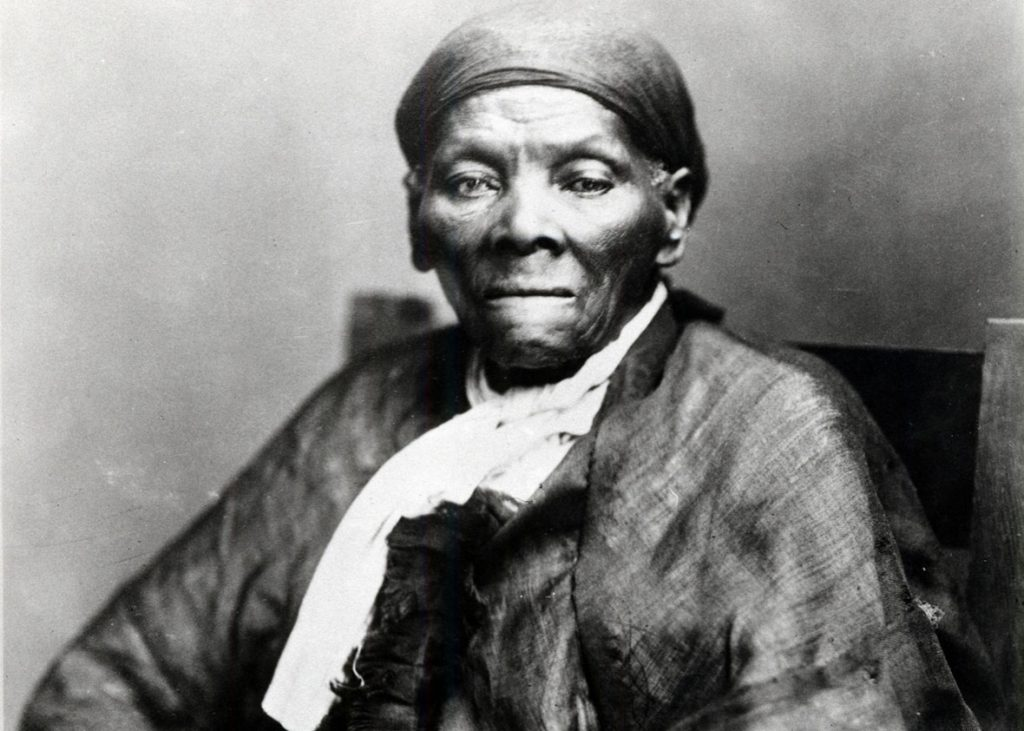 A photo of Hariet Tubman, an elderly African American woman missing her teeth, sitting in a chair, wearing a white scarf and a black scarf, as well as a dark tunic.