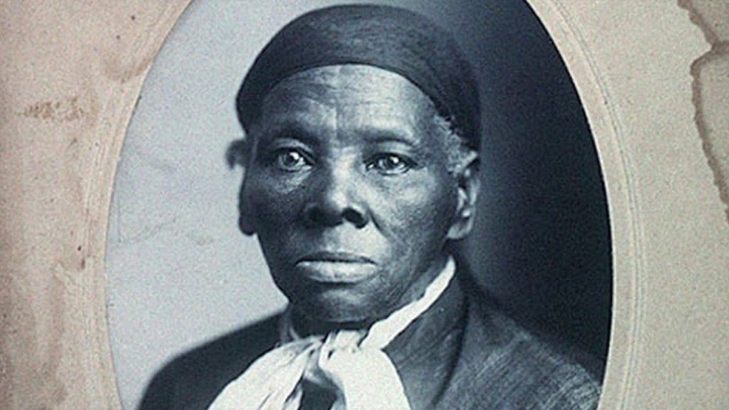 A rare black-and-white portrait photograph of Harriet Tubman, an elderly African-American woman wearing a head scarf, a white scarf around her neck, and a black tunic.