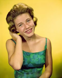A young Patty Duke, taken some time in the 1950s, wearing a green dress, with a head of blond hair against a yellow background.