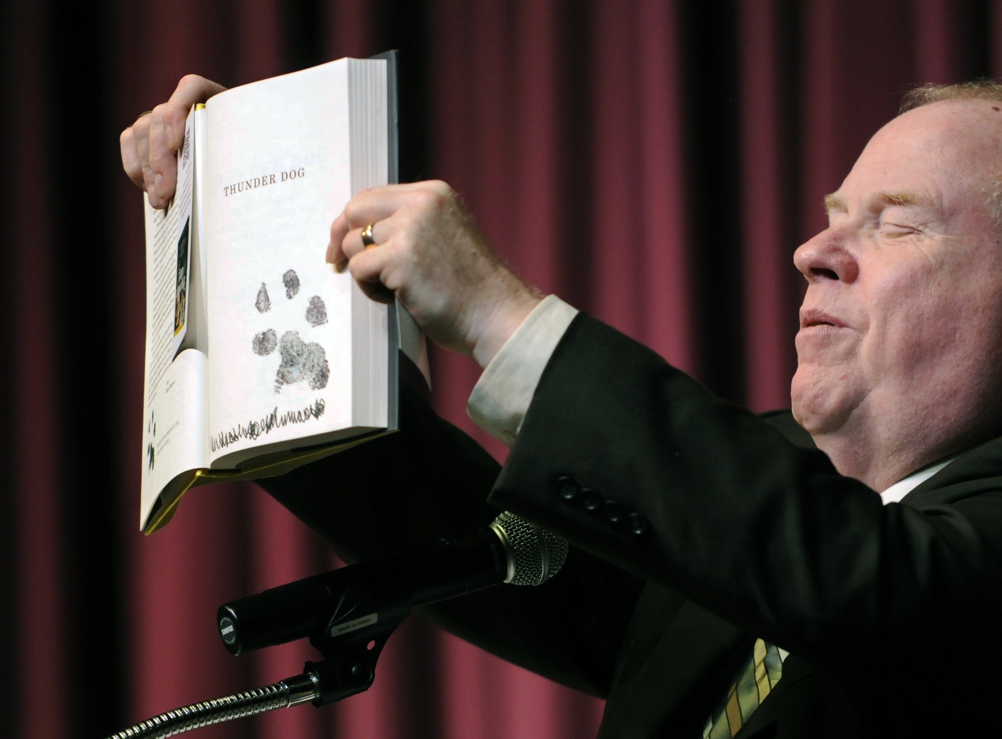 Speaking to Lincoln Southeast students and staff, Michael Hingson shows a paw print in his book Thunder Dog. Photo: Robert Becker