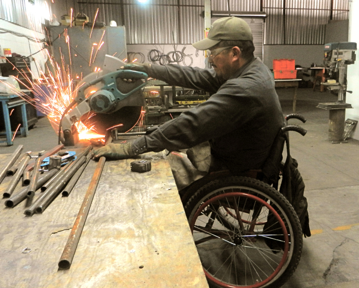 A worker in ARSOBO's wheelchair workchops creates the frame for a new chair.