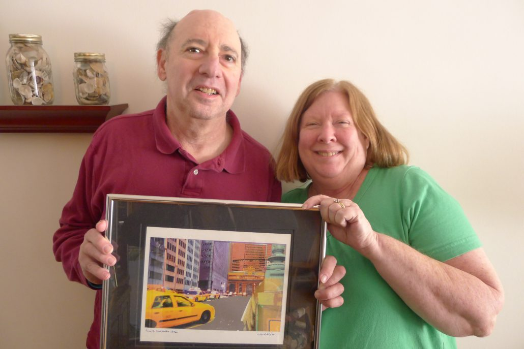 A balding man with silver hair  in a red collared shirt, and his wife, a blonde woman in a green t-shirt, smile at the camera and hold up a framed photo of the man's computer art, showing a New York