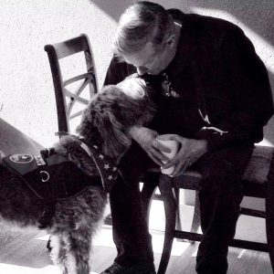 A black-and-white portrait of a middle-aged man sitting on a chair, rubbing noses with his shaggy service dog.
