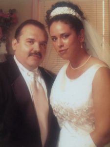 A middle-aged Latino man wearing a suit and his Latina daughter, wearing a wedding a dress on her wedding day.
