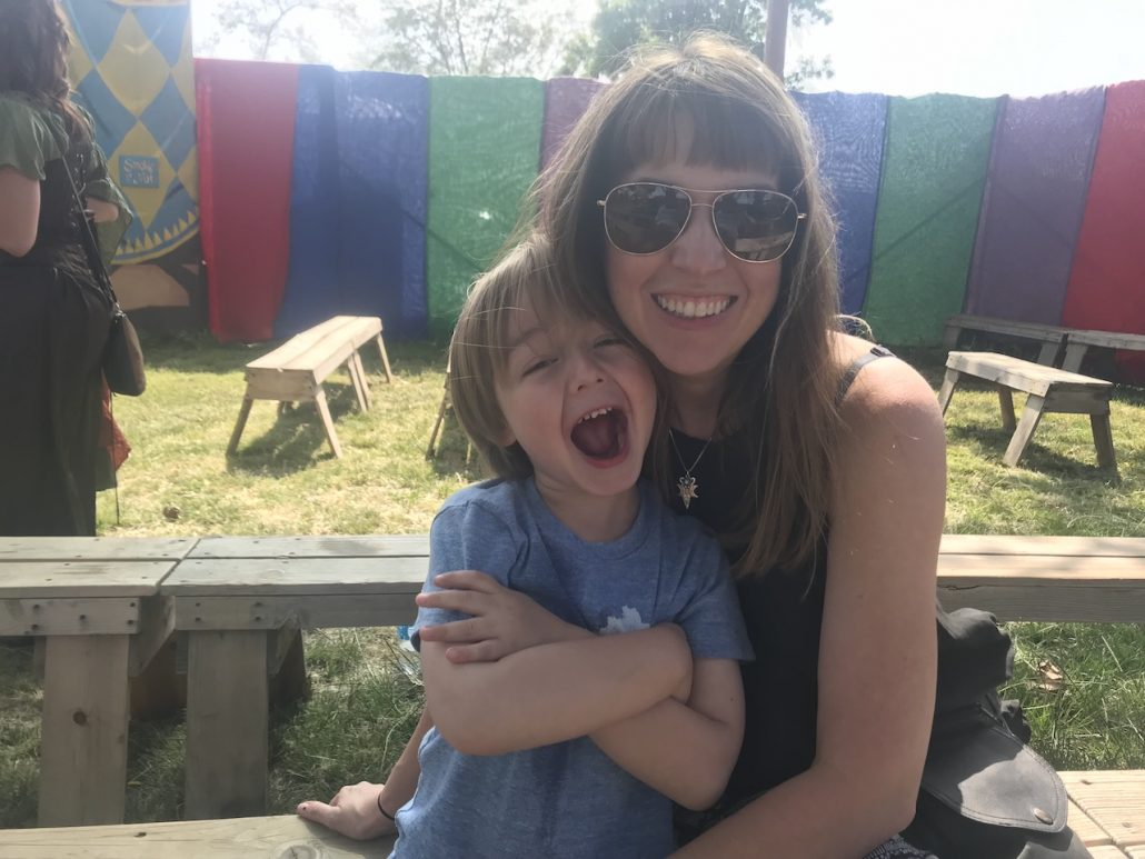 A mother and her four-year-old boy laugh together outside at a Renaissance Faire.