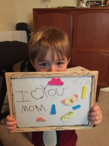 "A little boy with blond hair holds up a sign saying ""I love you Mom"""