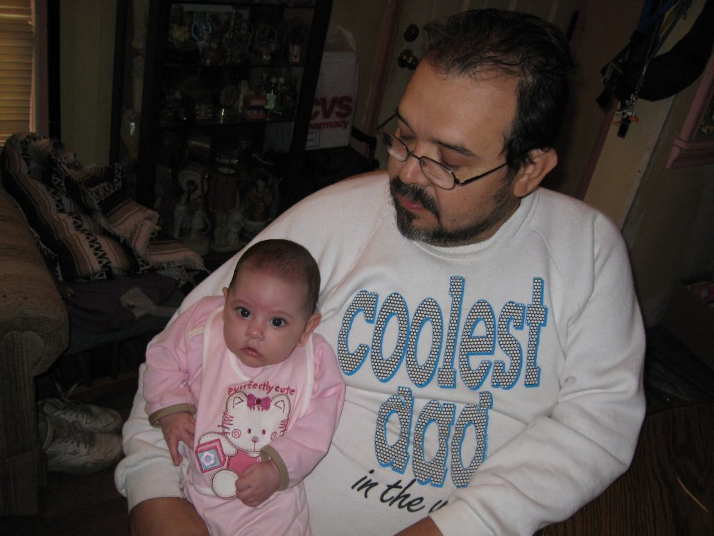 A little Latina girl, less than a year old, posing with a bearded Latino man in glasses, wearing a 'Coolest Dad' sweatshirt.
