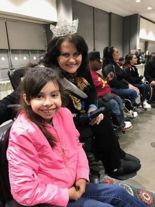 Miss Wheelchair America poses with a little girl in a pink jacket who is also in a wheel chair.