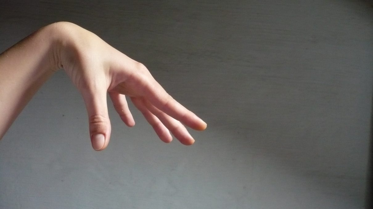 A delicate hand in front of a gray wall exhibit some hand motions typical of people with autis,.