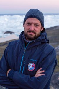 A man with a beard wearing a knitted cap and a blue sweat shirt, standing in front of glacial waters on a rocky beach.