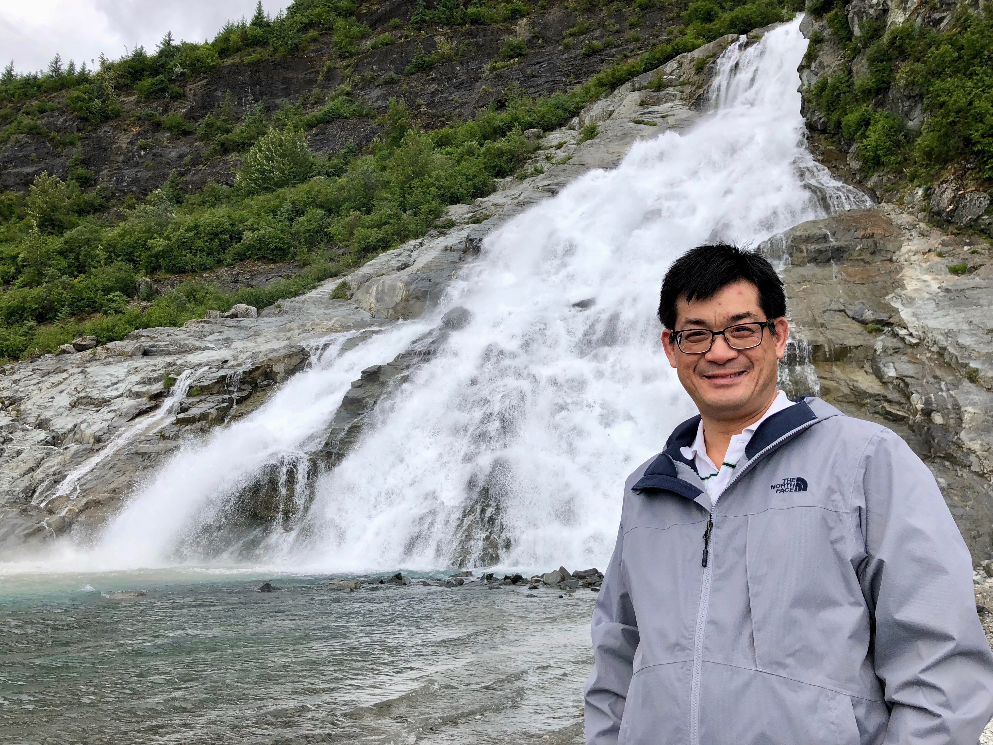 An Asian man in his thirties wearing glasses and a gray parka standing in front of a waterfall.