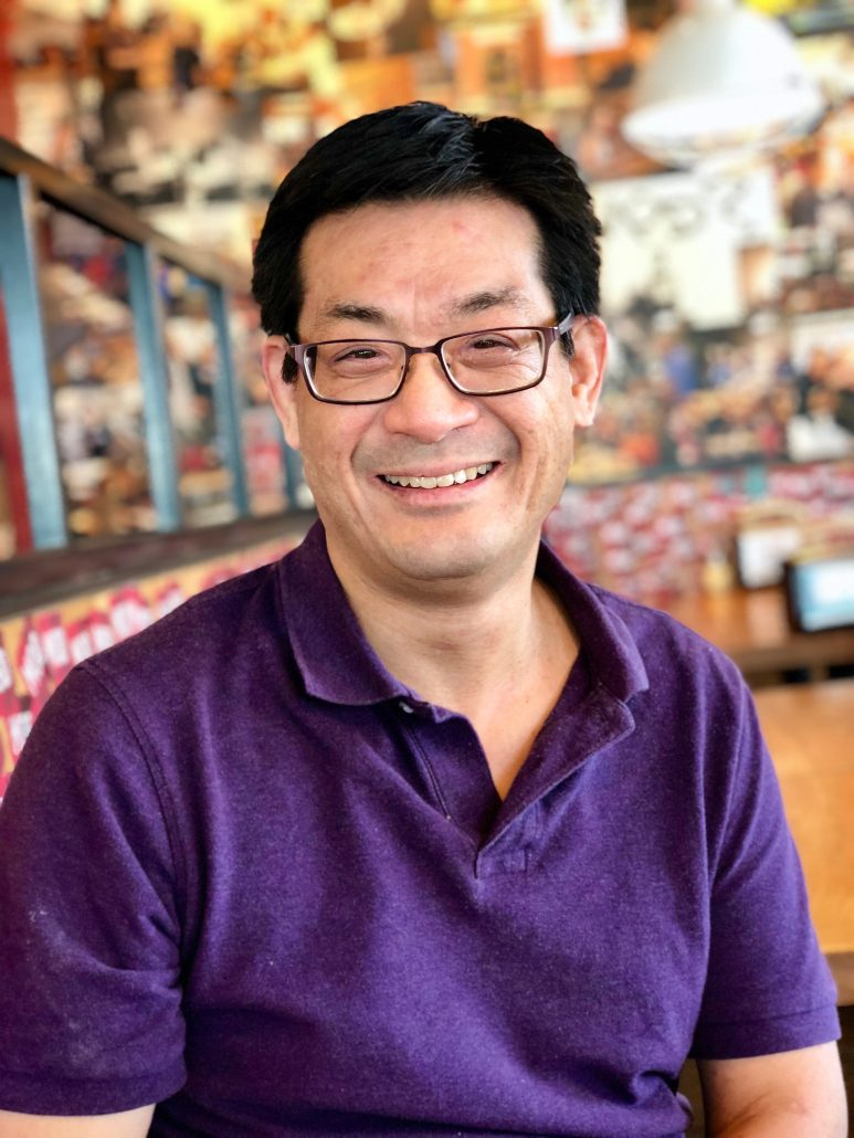 An Asian man wearing glasses dressed in a purple polo shirt.