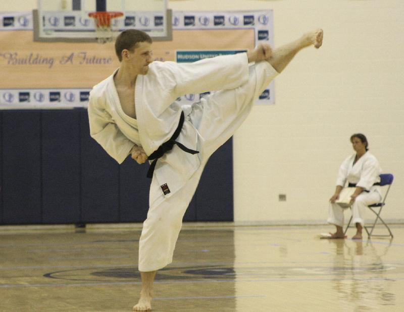 Jake Levitt, wearing a karate uniform, doing a karate kick at a dojo.