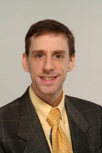 A headshot of Jake Levit, a white man with closely cropped brown hair, wearing a brown suit, a gold shirt, and a gold tie.