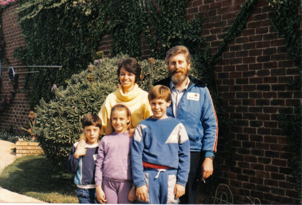 A vintage family photo of a bearded man in a blue jacket, an attractive woman with dark hair in a yellow turtleneck, and their three children, including two young boys and a girl.