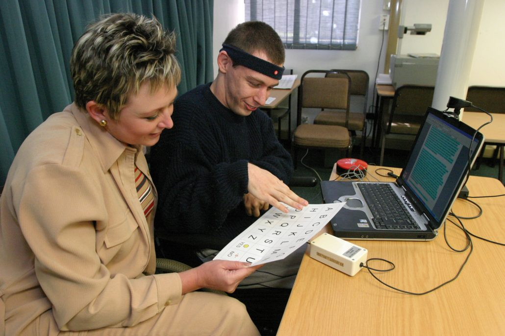 A man in a wheelchair with a headband hooking him up to a computer while a woman in a gold pant suit looks on.