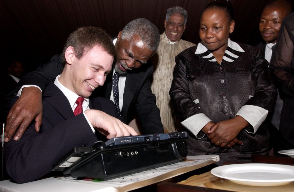 A white man with brown hair in a wheelchair, showing South African president Thabo Mboki the computer he uses to communicate.