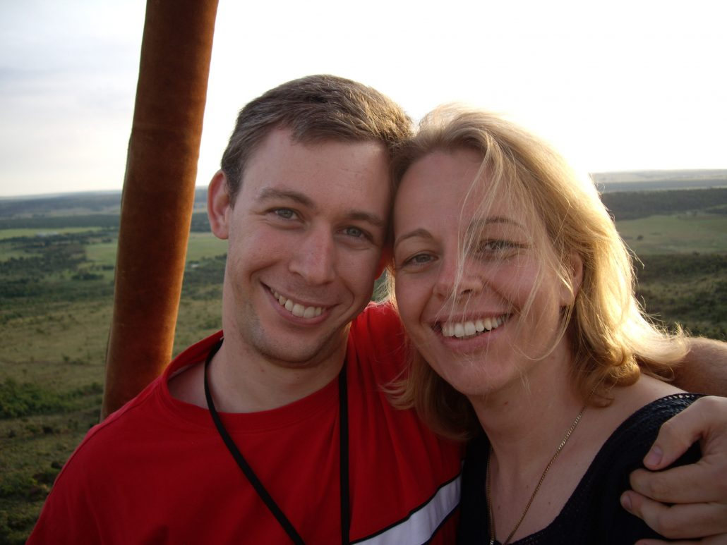 A man with brown hair and a red t-shirt standing with his blond wife against a pastoral background in the middle of the daytime.