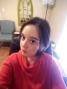 A woman in a red sweater with chin-length brown hair posing for the camera in her living room with a blue chair in the background.