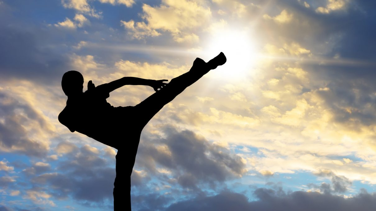 The silhouette of a man doing a karate kick against a clouded sky at sunrise.