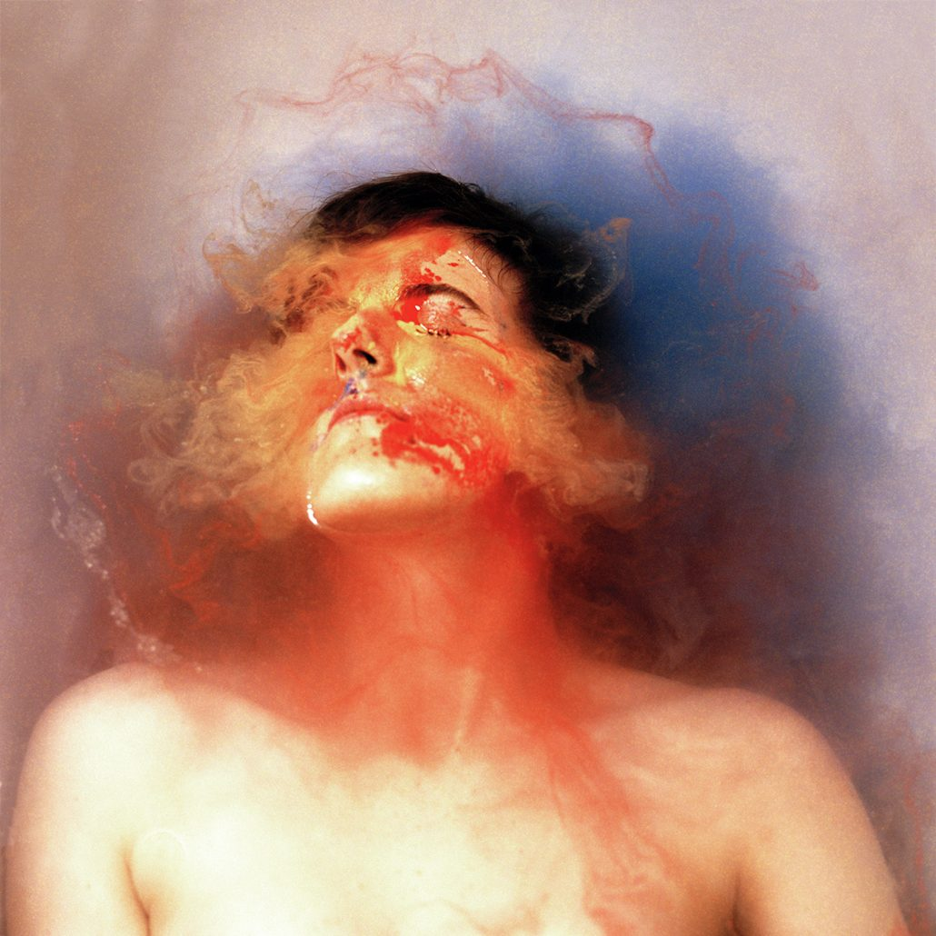 A woman with her face underwater in a bathtub, bleeding from her mouth into the water.