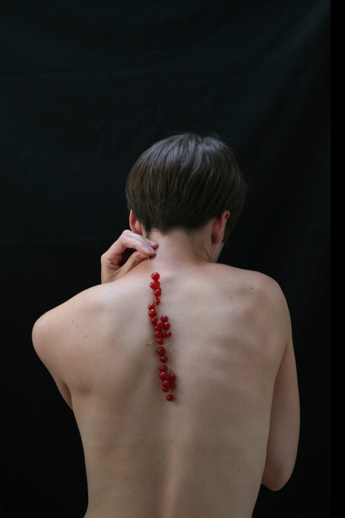 An artistic photograh of a nude woman standing with her back to the camera with a cut down her spine.