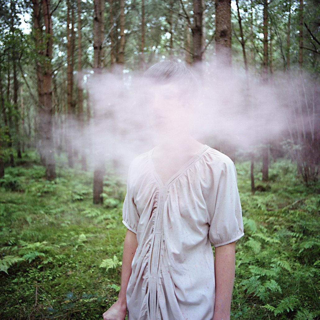 A woman standing in the forest with a cloud of smoke hanging before her face.