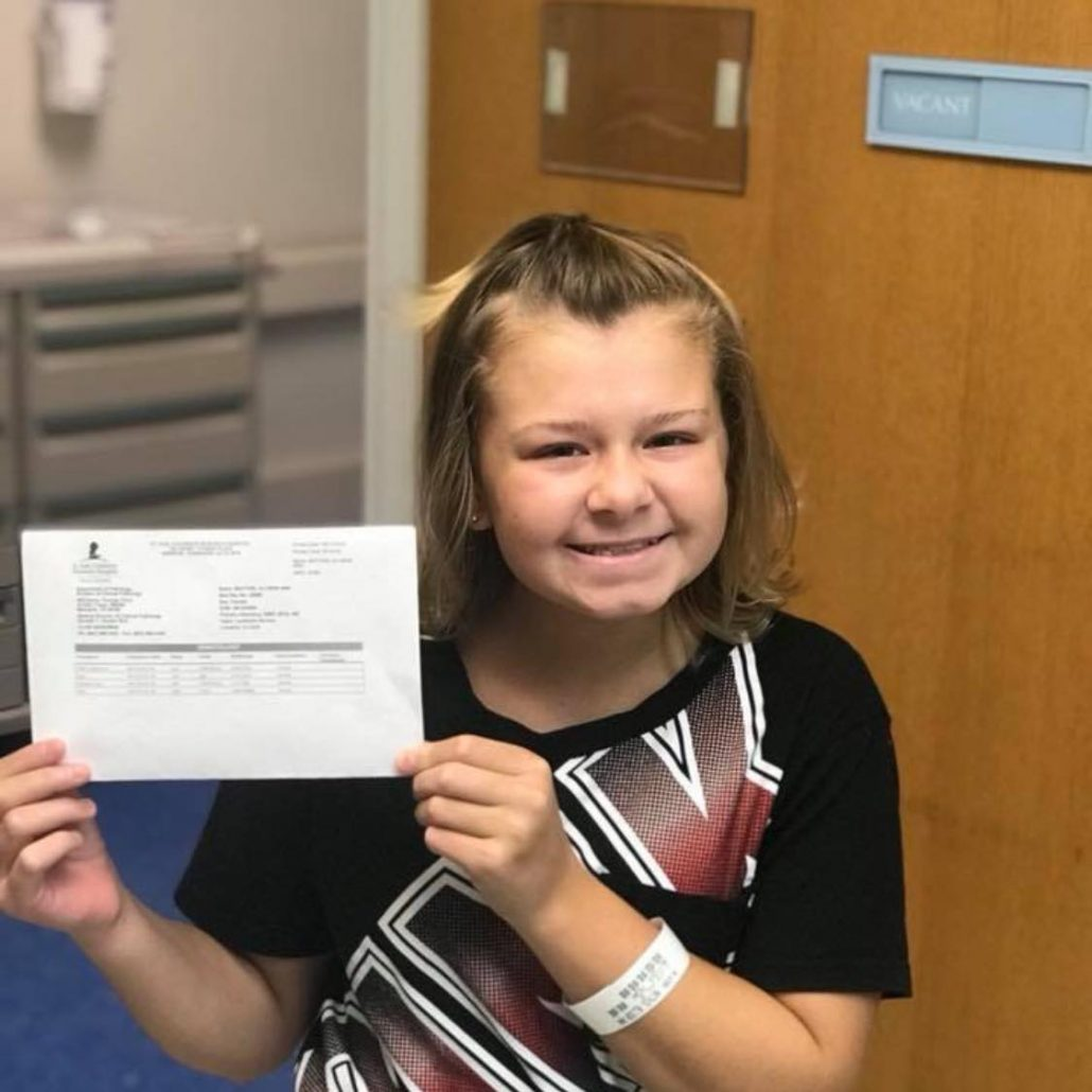 A little blonde girl smiles as she holds up a certificate showing that she has successfully undergone chemotherapy.