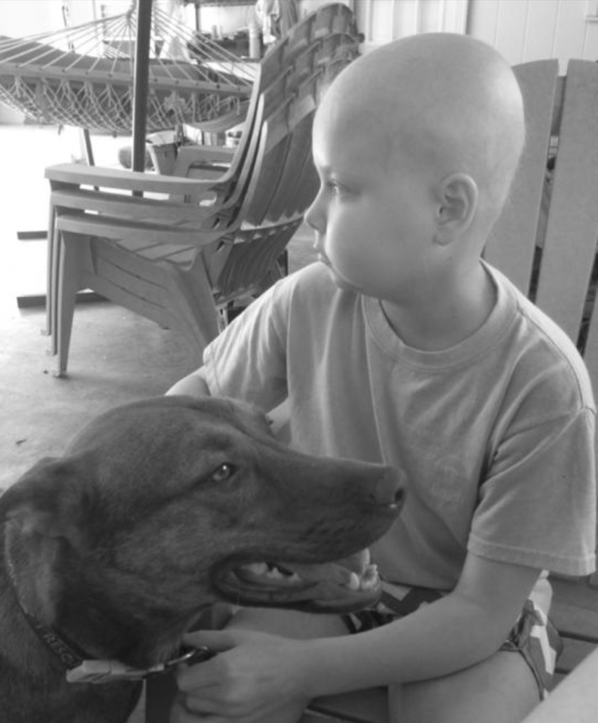 A girl without hair in the midst of chemo treatment pets a brown dog.