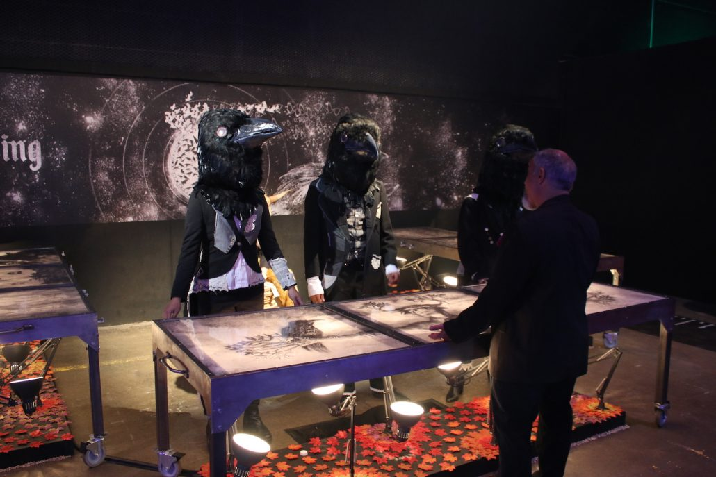 Three people wearing crow head masks stand behind a table.