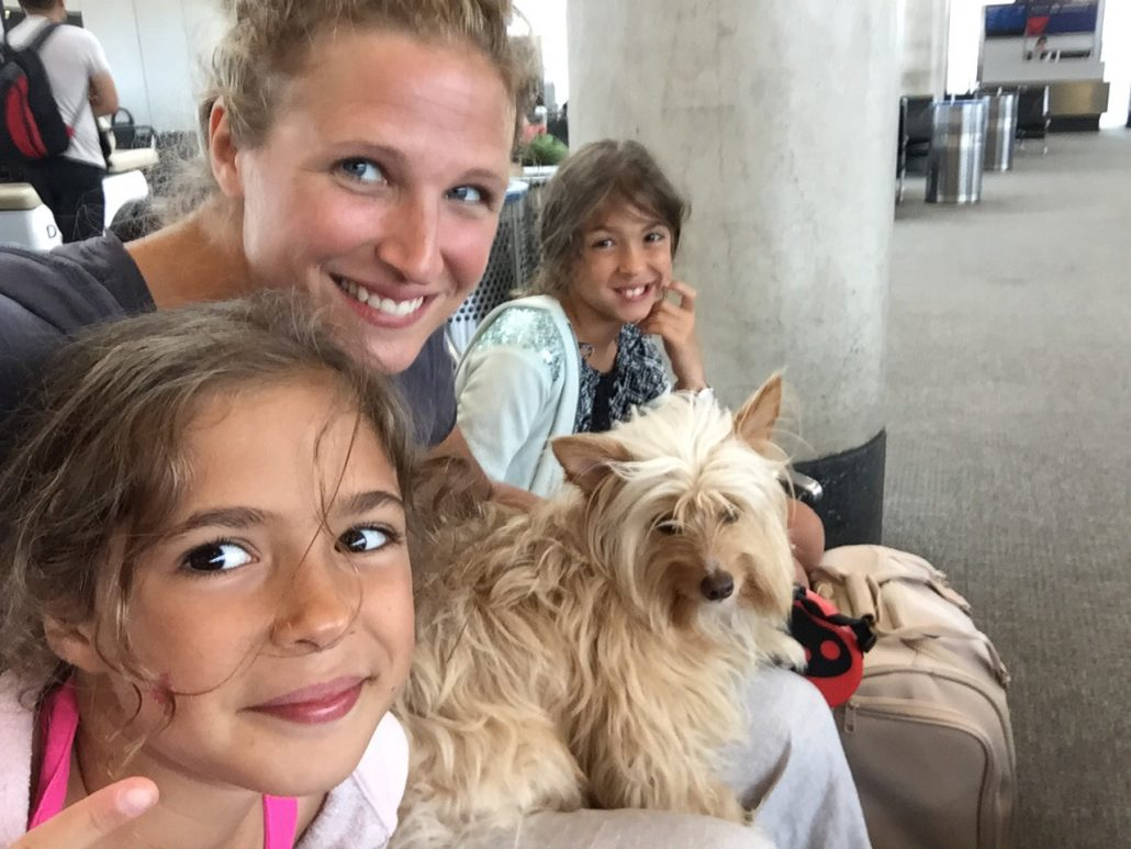A picture of a mom with two twin nine-year old girls posing with a shaggy scotty dog.