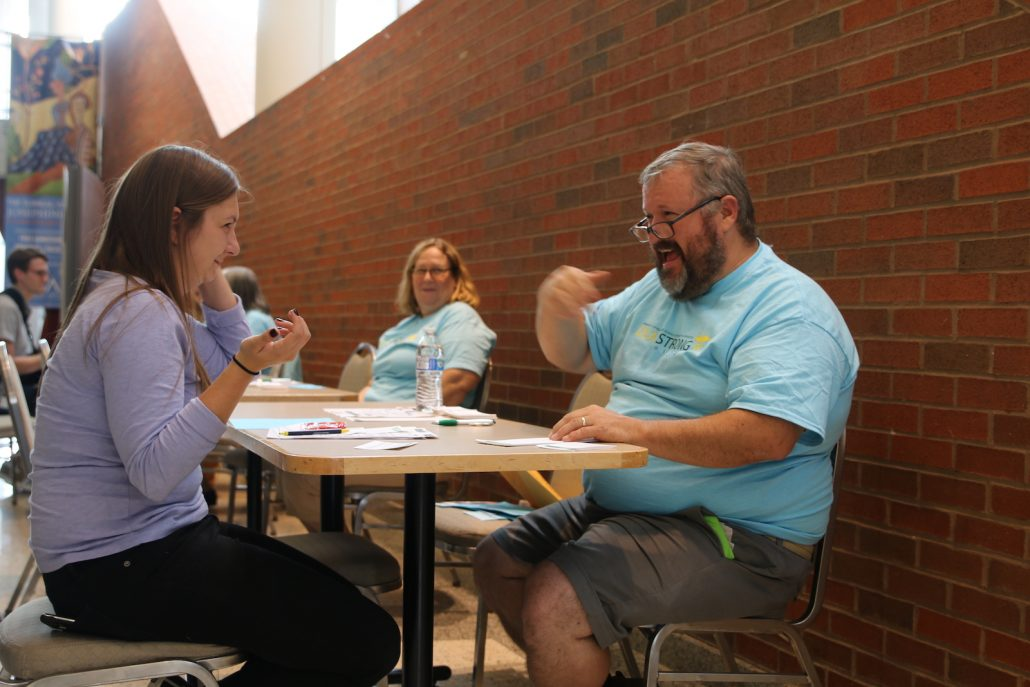 A deaf man in glasses wearing a blue shirt has a conversation in sign language with an older brunette in a purple top.
