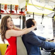 A beautiful woman in a red dress covers the eyes of a bus driver.