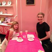 A blonde woman with short hair having tea in an all-pink room.