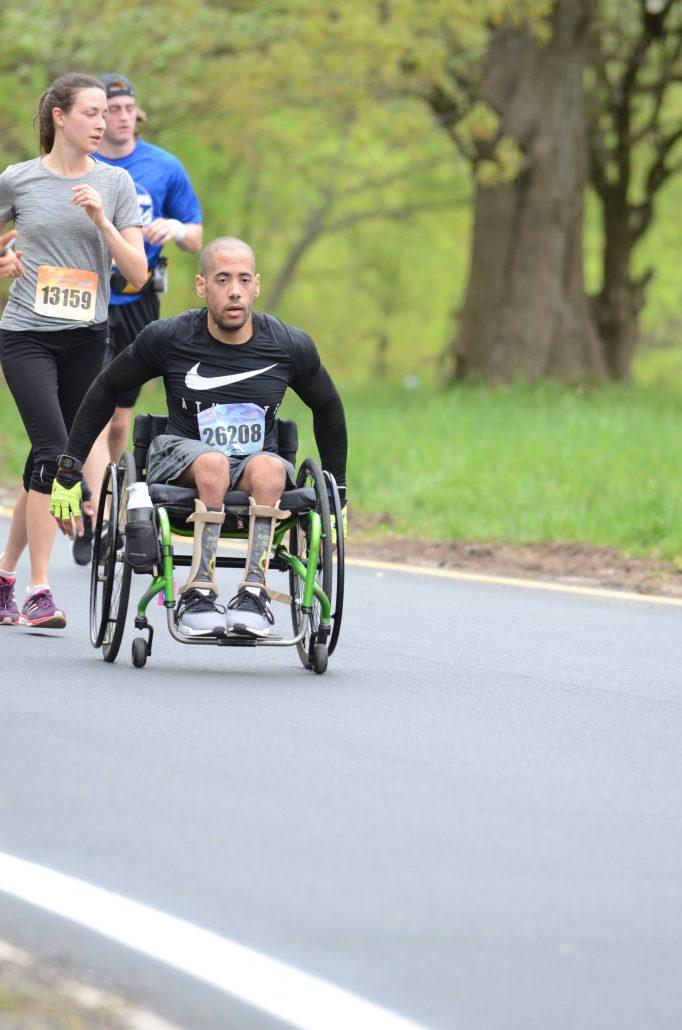 A black man with spina bifida in a wheelchair racing in a marathon.
