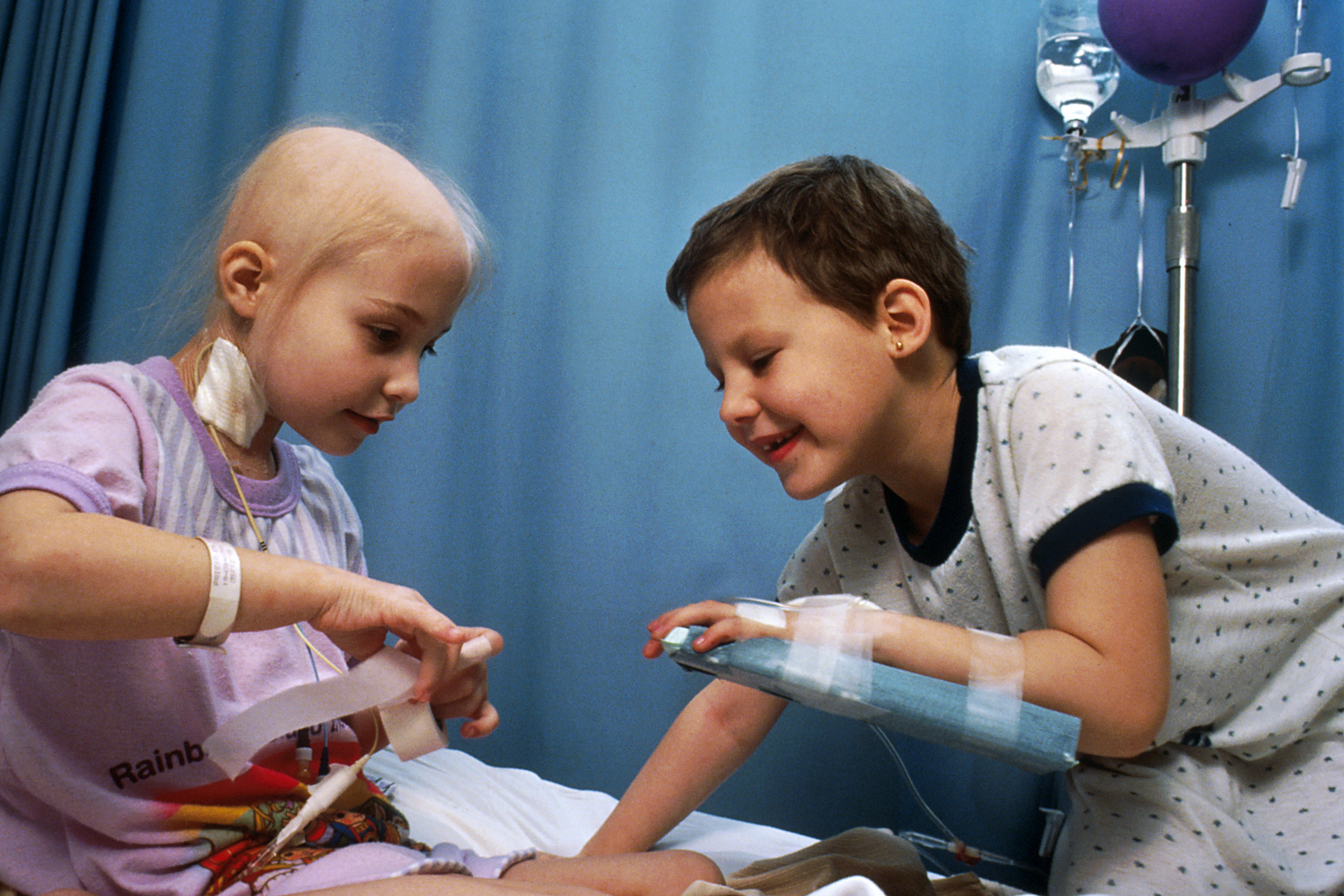 A little girl playing with a friend in a hospital bed as they await chemotherapy treatment.