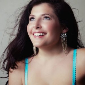 A beautiful girl in an aqua tank top with brown hair and glittery earings smiles and looks up.