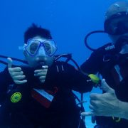 A disabled man giving a thumbs up sign underwater in scuba gear, alongside his diving instructor.