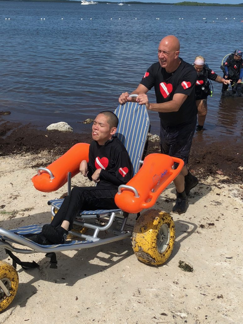 An older man with a shaved head in scuba gear helps a disabled man in a wheelchair into the water,