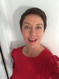 A woman with short brown hair in a red shirt.