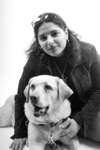 A young, attractive Muslim-American woman with her guide dog.