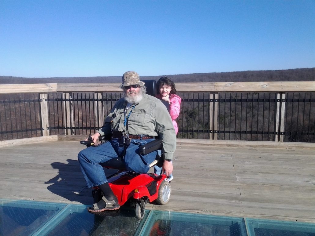 A man with a beard in a powered wheelchair going geocaching with his daughter.
