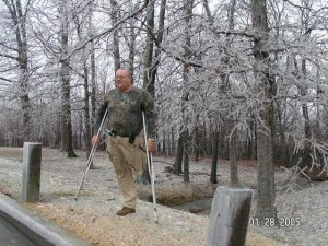 A one-legged man on crutches wearing camo and hunting for geocaches in the woods.