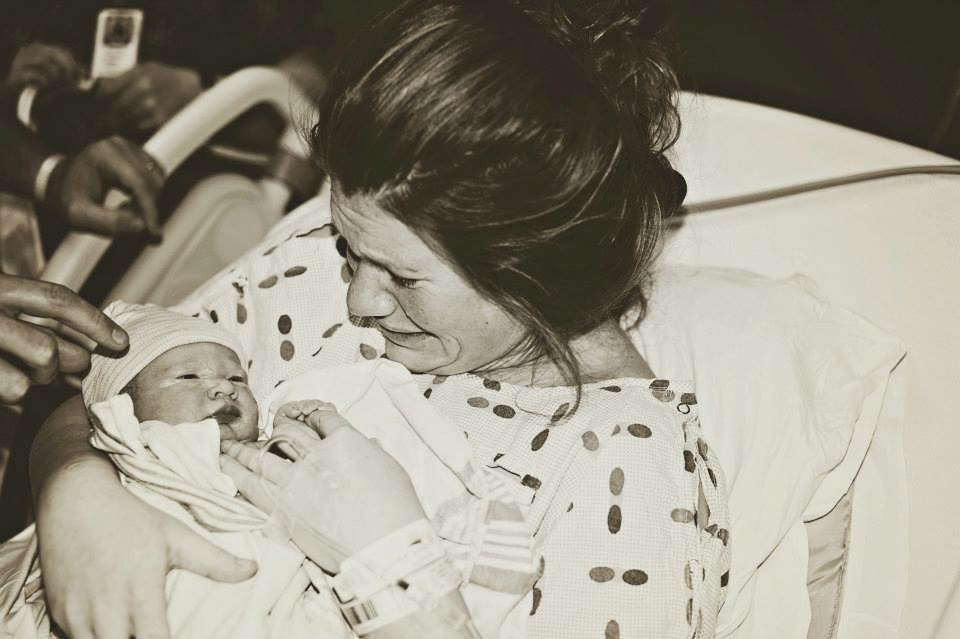 A woman holds her newborn baby while crying immediately after birth.