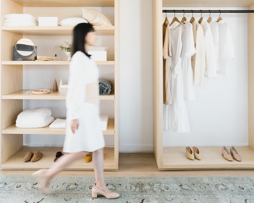 Marie Kondo walking by a neatly organized closet.
