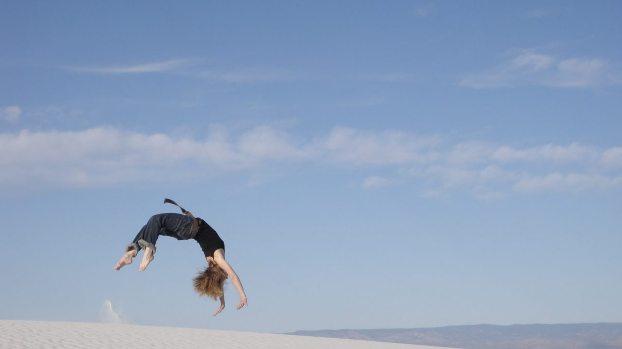 A woman flipping head over heels on a sand dune or beach.