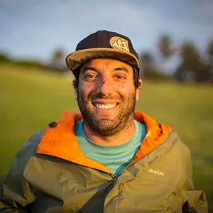 Alvero Silverstein, co-founder and CEO of Wheel The World, smiles at the camera. He is wearing a baseball cap, is unshaven, and is wearing a brown jacket with an orange collar.