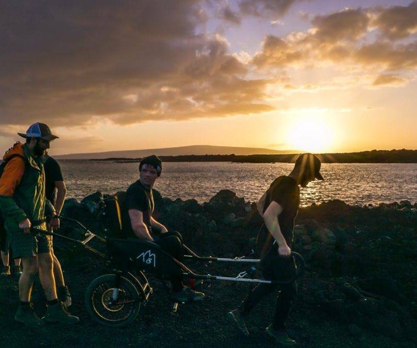 Two friends helping a disabled man hike on a beautiful trail at sunset.