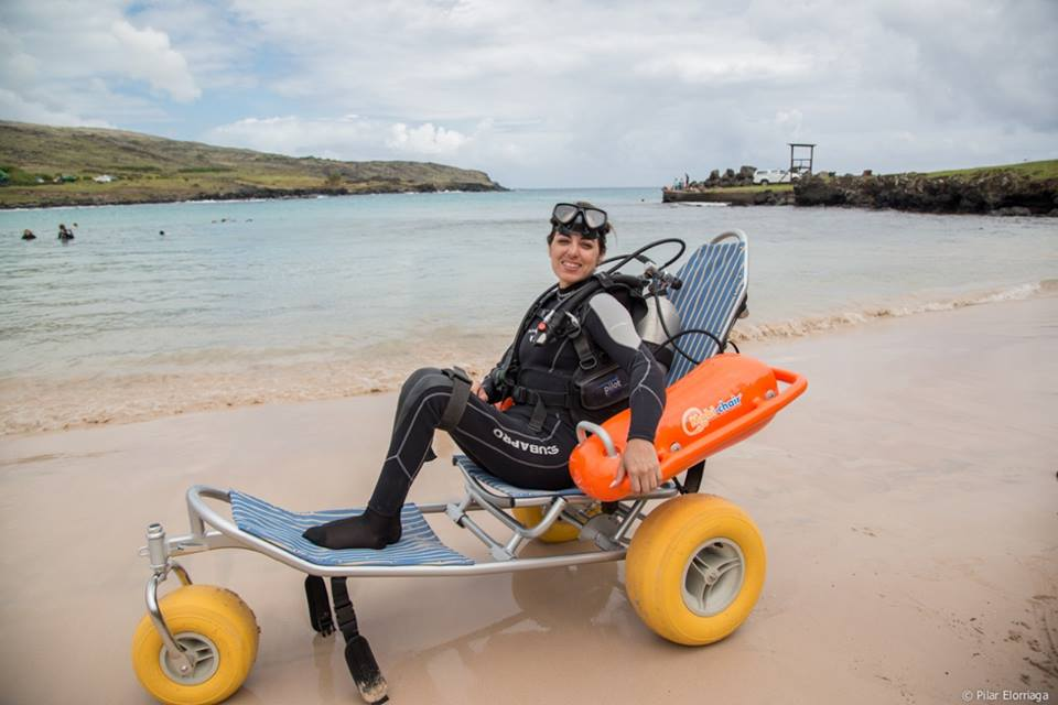 A smiling disabled woman in a custom-built wheelchair for getting into the wall with scuba diving. The chair has three big yellow wheels and floats. She smiles at the camera wearing full scuba gear, with the beach behind her.