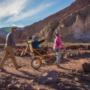 A male and female hiker helping a disabled man in a custom-built hiking wheelchair traverse a rocky landscape.
